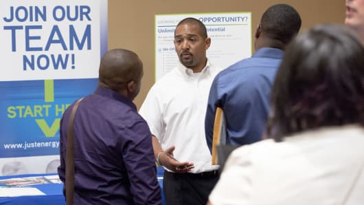A Just Energy Group representative speaks with job seekers during the Best Hire Career Fair in Houston, Texas.
