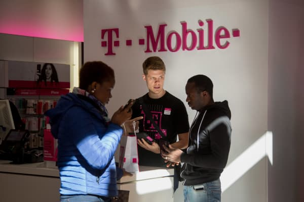 An employee, center, assists customers at a T-Mobile US store in New York.
