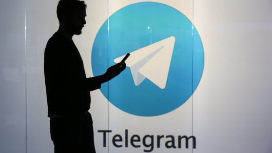 A man is seen as a silhouette as he checks a mobile device whilst standing against an illuminated wall bearing Telegram's logo.