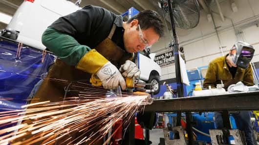 Workers make brackets for Chevrolet Express Vans at VIA Motors in Orem, Utah.