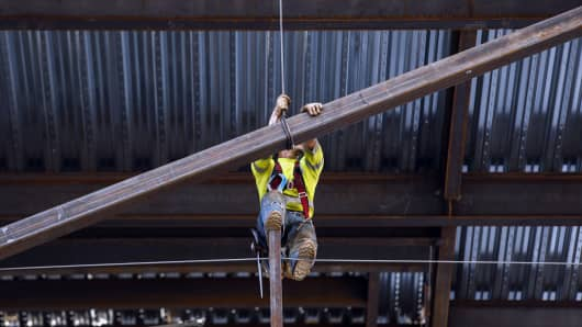 A contractor guides a steel beam into place while working on the Korean Air Lines Co. Wilshire Grand hotel and office building in downtown Los Angeles, California.