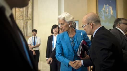 International Monetary Fund (IMF) managing-director Christine Lagarde (C) shakes hands with Turkey's Deputy Prime Minister Mehmet Simsek (R) at the G20 finance ministers meeting in Chengdu, in China's Sichuan province on July 24, 2016.