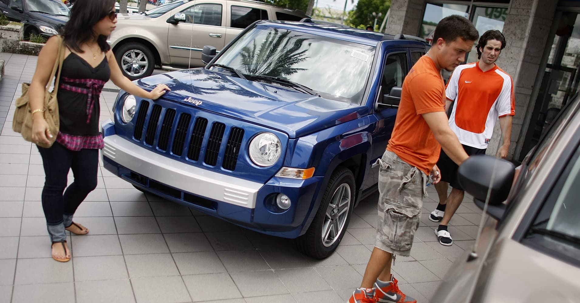 Customers look at a Jeep vehicle for sale on the sales lot of a Chrysler Jeep Dodge dealership in Miami.