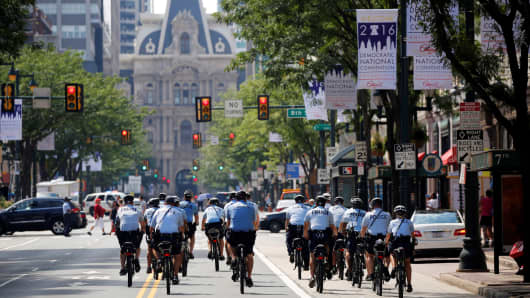 Police ride bicycles down Market Street toward City Hall ahead of the Democratic National Convention in Philadelphia, July 24, 2016.