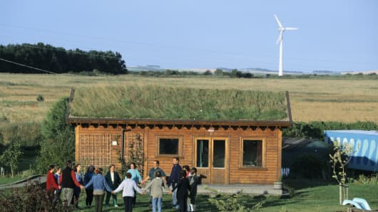 Residents at Findhorn Ecovillage, an environmentally friendly, self sufficient community, meditate in a circle by their grass roof cabin, Scotland.
