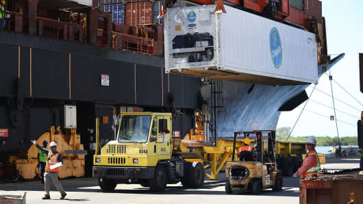 Shipping containers are offloaded from a cargo ship at Port Everglades on June 24, 2016 in Fort Lauderdale, Florida.