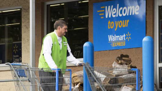 An employee retrieves shopping carts at a Wal-Mart Express store in Richfield, North Carolina.
