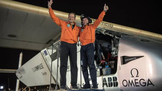 Solar Impulse 2 pilots Bertrand Piccard (R) and Andre Borschberg (L) waves to the crowd after landing in Abu Dhabi to finish their world flight on July 26, 2016.