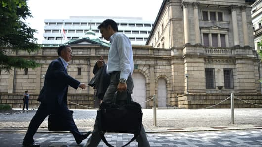 Businessmen walk past the Bank of Japan in Tokyo, Japan