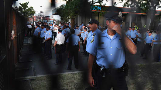 Police watch protesters near the Wells Fargo Center on July 26, 2016, in Philadelphia.