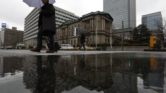 Pedestrians holding umbrellas while walking past the Bank of Japan (BOJ) headquarters are reflected in a puddle in Tokyo, Japan. Markets expect the Japanese central bank to introduce further stimulus measures on Friday, July 29, 2016, in a bid to prop up Japan's flagging economy.