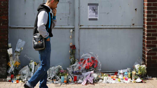 A man walks past floral tributes and a note including a picture of French priest Jacques Hamel, killed on July 26 in the church during a hostage-taking claimed by Islamic State group.