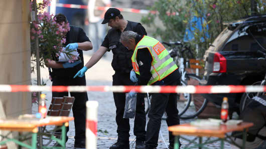 Police investigators work at the site of a suicide bombing in Ansbach, southern Germany, on July 25, 2016.
