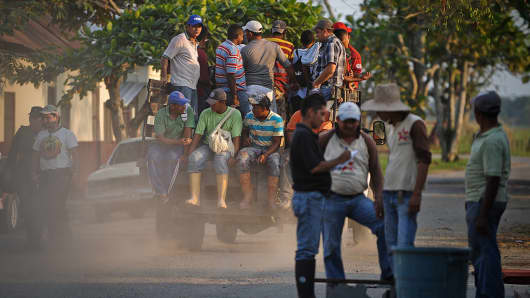 Workers ride on a pickup truck toward farm land in Santa Barbara de Zulia in Venezuela.