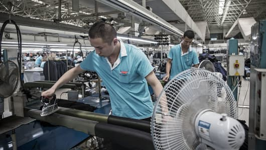 Employees iron fabric at a factory operated by the Shandong Ruyi Technology Group in Jining, China.