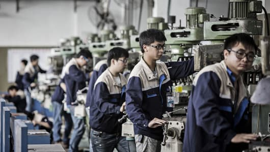 Workers operate machinery on the assembly line at a Lyric Robert factory, operated by Guangdong Li Yuanheng Intelligent Automation Co., in Huizhou, Guangdong province, China, on Monday, April 18, 2016.