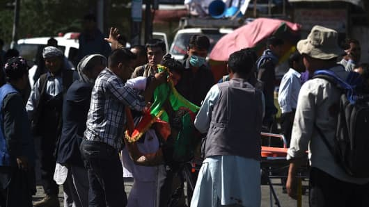 Volunteers carry the body of a victim after a separate blast that targeted crowds of minority Shiite Hazaras during a demonstration on July 23, 2016.