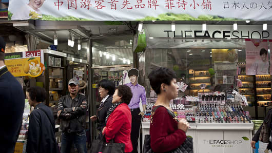 Shoppers walk past a cosmetics store displaying a banner written in Chinese in the Namdaemun market in Seoul, South Korea, on Oct. 24, 2012.