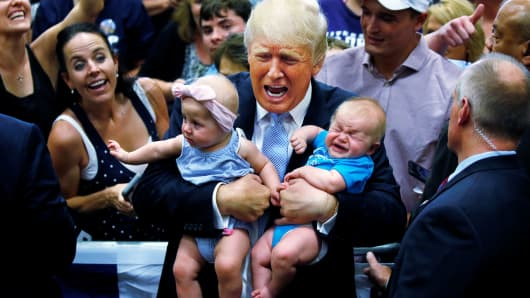 Republican presidential nominee Donald Trump holds babies at a campaign rally in Colorado Springs, July 29, 2016.