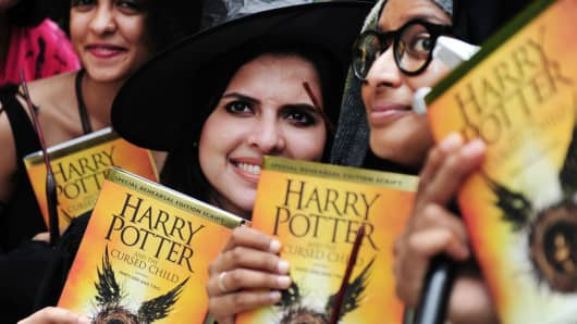 People pose for photgraphers with copies of J.K. Rowlings new book 'Harry Potter and the Cursed Child' during an event to mark the book launch at a mall in Chennai, India on July 31, 2016.