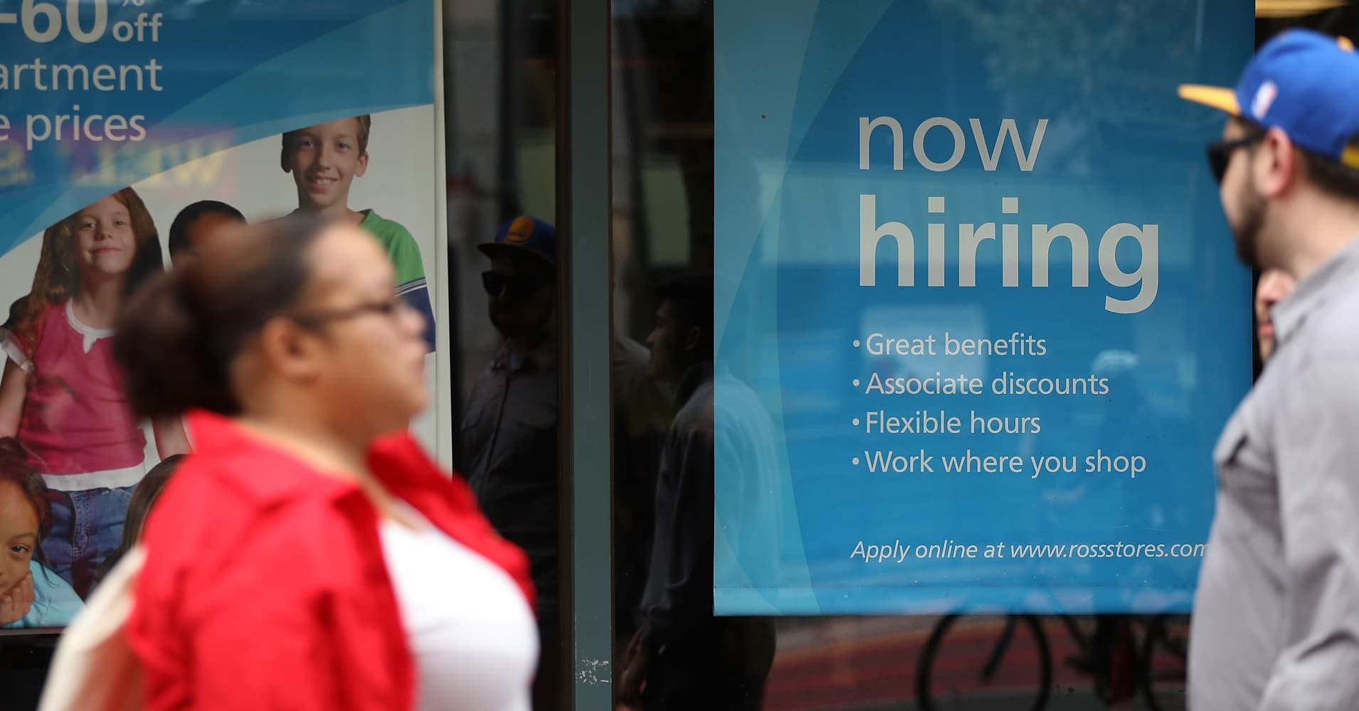"A ""now hiring"" sign is posted outside a store in San Francisco."