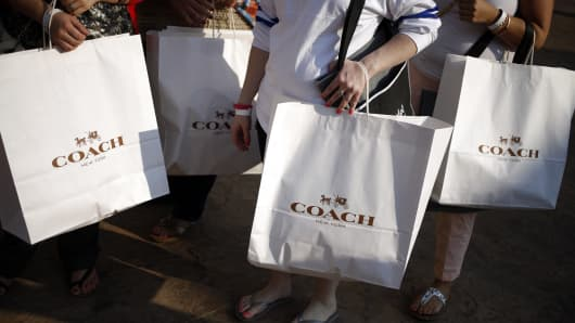 Customers carry Coach Inc. shopping bags after shopping at a store during a charity preview event on the eve of the grand opening of the Outlet Shoppes of The Bluegrass in Simpsonville, Kentucky.