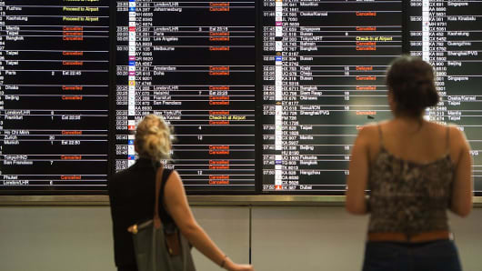 Passengers look at an information board displaying a list of cancelled and delayed flights in Hong Kong on August 1, 2016, shortly after a 'T8' storm signal was raised for Typhoon Nida.