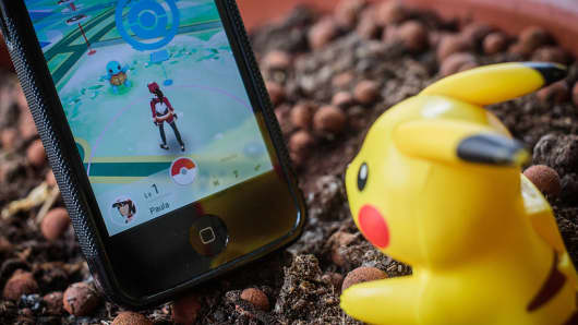 A Pikachu toy sits next to a smartphone with the PokemonGo app.