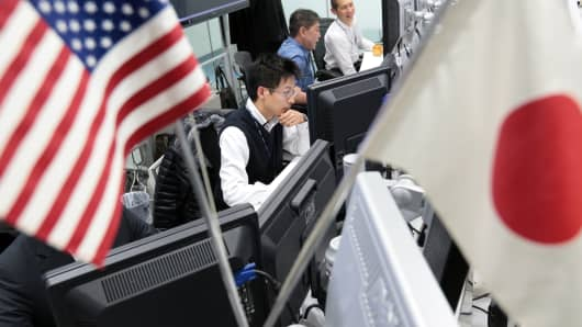 A dealer works behind U.S., left, and Japanese national flags at a foreign exchange brokerage in Tokyo, Japan.