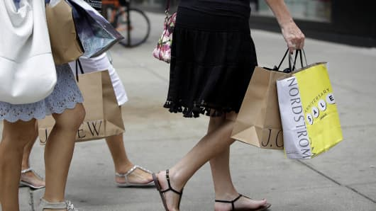 Consumers hold shopping bags as they walk along Michigan Avenue in Chicago.