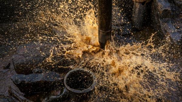 Crude oil sprays from a well bucket.
