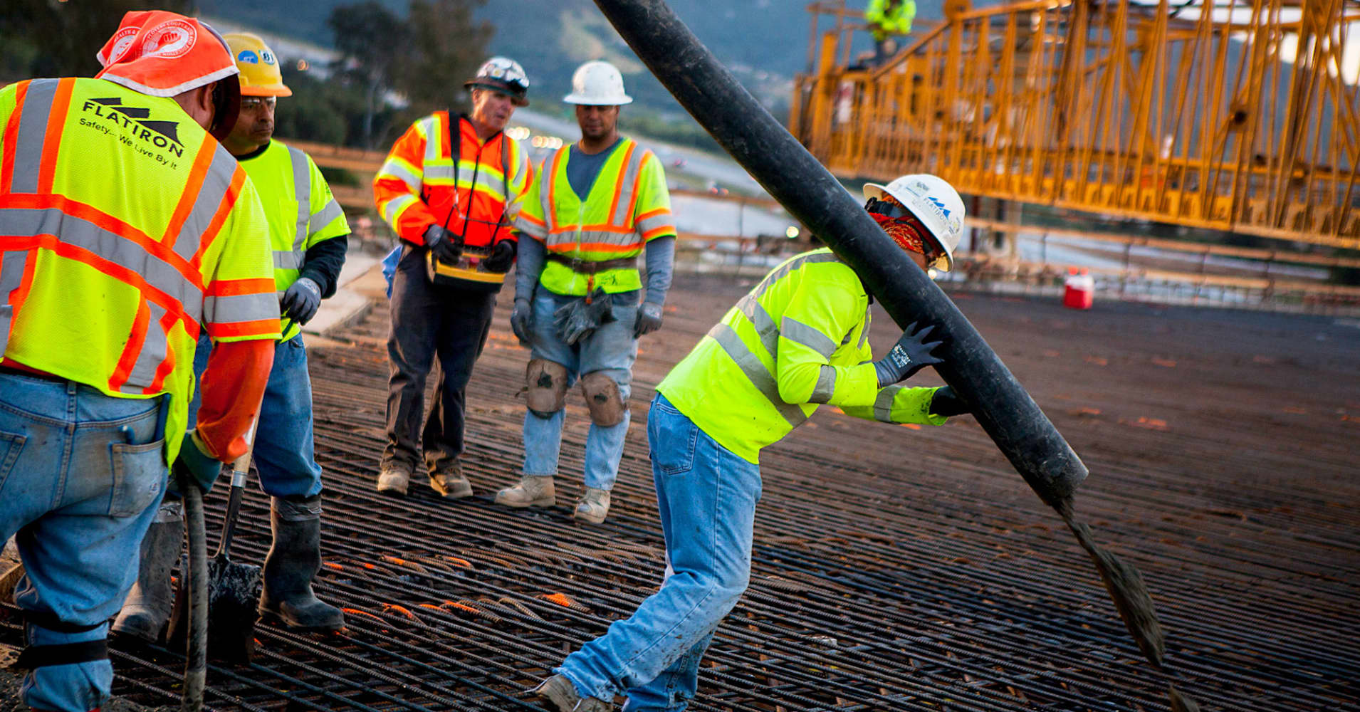 Construction workers pour concrete as part of a bridge expansion project in California.