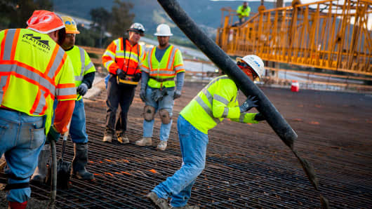 Construction workers pour concrete as part of a bridge expansion project in California.