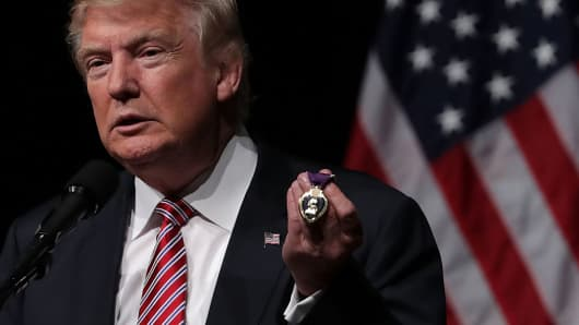 Republican presidential nominee Donald Trump holds a Purple Heart, given to him by veteran Louis Dorfman, during a campaign event at Briar Woods High School August 2, 2016 in Ashburn, Virginia