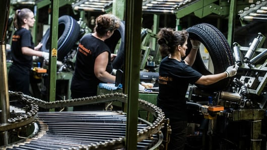 Workers inspect tires at the Continental plant in Romania