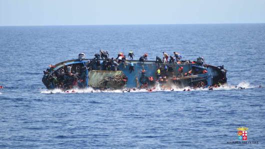 Migrants in an overcrowded boat about to capsize are rescued by the Bettica and Bergamini ships of the Italian Navy in the Sicilian Strait (between Libya and Italy) on May 25, 2016.