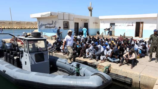 Illegal migrants sit on the dock at the Tripoli port after 117 migrants of African origin, including six pregnant women, were rescued by two coast guard boats off the coast of Libya on June 7, 2016.
