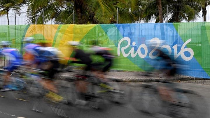 Cyclists ride by a Rio 2016 sign