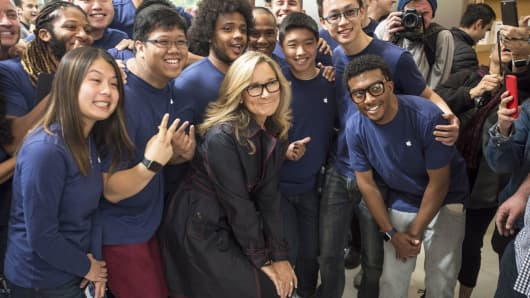 Angela Ahrendts, senior vice president of retail at Apple, center, stands for a photograph with employees during the grand opening of the company's new flagship store at Union Square in San Francisco, May 21, 2016.