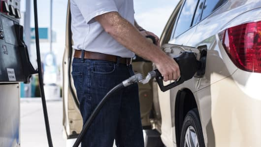 A man pumps gas into his car at a Chevron gas station in Albuquerque, New Mexico.