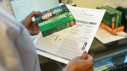 A nurse practitioner holds a box of insect repellent and information on mosquito protection that she gives her pregnant patients at the Borinquen Medical Center, Tuesday, Aug. 2, 2016 in Miami.