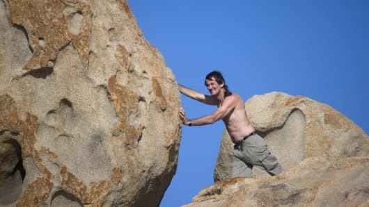 Man pushing boulder up a hill