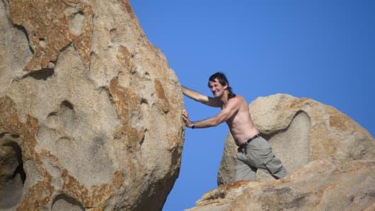 Man pushing boulder up a hill