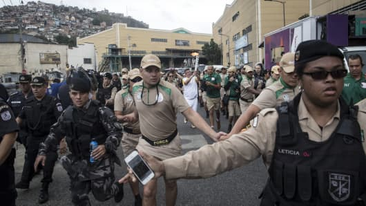 Brazillian police and military surround Olympic torch relay runner Milton Cunhaas he made his way from Cidade do Samba in central Rio de Janeiro Wednesday morning.