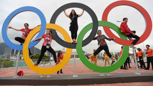 People pose with the Olympic rings at the Olympic Park in Rio de Janeiro, on August 3, 2016.
