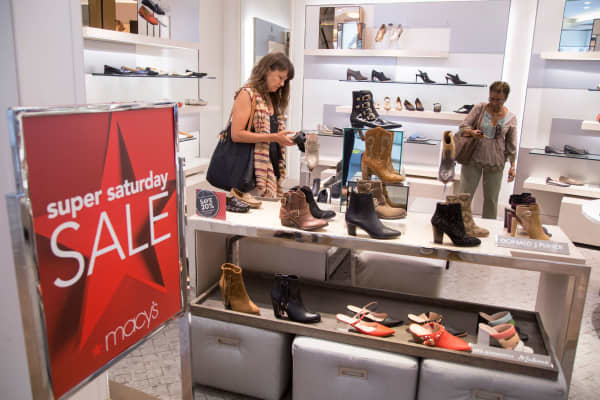 Shoppers look at shoes at a Macy's department store in New York.