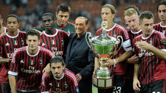 Players of AC Milan and AC Milan chairman Silvio Berlusconi celebrate after winning the Berlusconi Trophy during the Berlusconi Trophy match between AC Milan and Juventus FC at Giuseppe Meazza Stadium on August 21, 2011