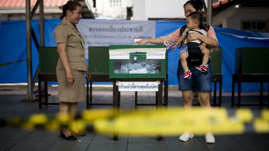 A Thai woman casts her ballot with her child at a polling station in Bangkok on August 7, 2016.