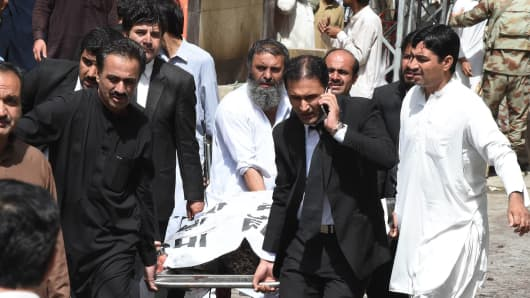 Pakistani lawyers carry the body of a colleague on a stretcher after a bomb explosion at a government hospital premises in Quetta.
