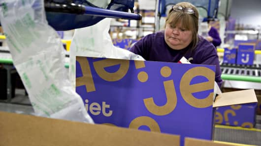 An employee packs a customer order before sealing the package for shipment at the Jet.com fulfillment center in Kansas City, Kansas.